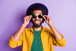 Photo of dreads hairdo dark skin person arms touch sunglass beaming smile isolated on violet color background