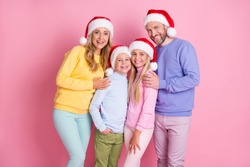 Photo of dream family mommy daddy two small kids wear x-mas santa claus cap isolated on pastel pink color background