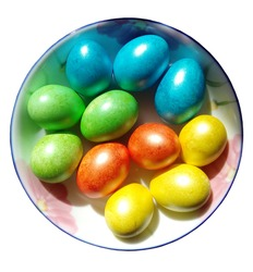 Photo of Easter dyed eggs. Twelve colored eggs on a plate, isolated on a white background. Pearl shine of green, red, blue and yellow colors.
