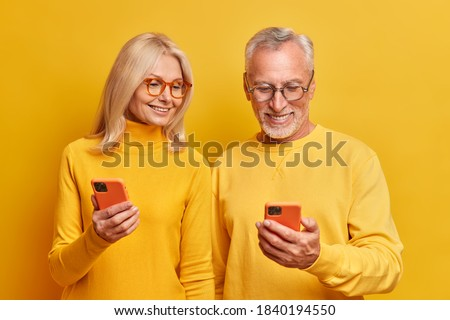 Photo of elderly grandmother and grandfather view photos together on smartphone devices watch interesting funny video online dressed in casual yellow turtlenecks pose indoor. Age and technology