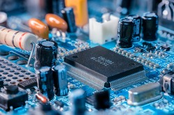 Photo of  electric component in electronic device, contain black microchip as main object, black capacitor and big resistor on blue printed circuit board. Captured using focus stacking method