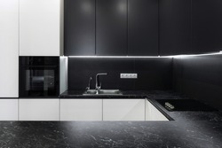 Photo of elegance interior in new hotel apartment. Modern black kitchen furniture with steel water tap, light and electric stove on table
