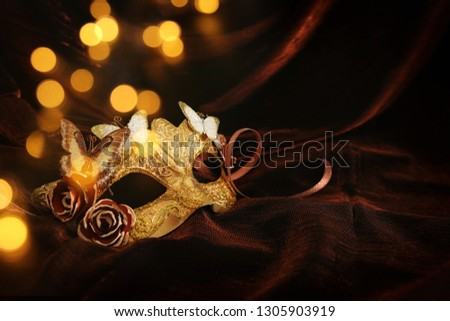 Photo of elegant and delicate gold venetian mask over dark silk background #1305903919