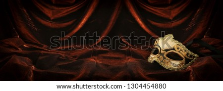 Photo of elegant and delicate gold venetian mask over dark velvet and silk background #1304454880