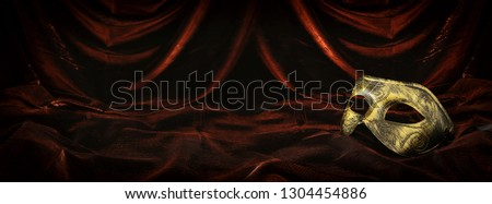 Photo of elegant and delicate gold venetian mask over dark velvet and silk background #1304454886