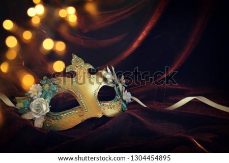 Photo of elegant and delicate gold venetian mask over dark velvet and silk background #1304454895