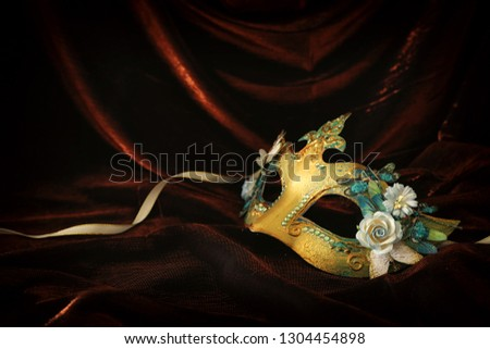 Photo of elegant and delicate gold venetian mask over dark velvet and silk background #1304454898