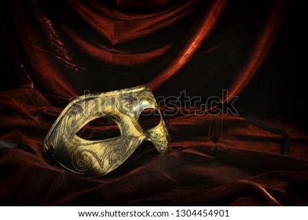 Photo of elegant and delicate gold venetian mask over dark velvet and silk background #1304454901
