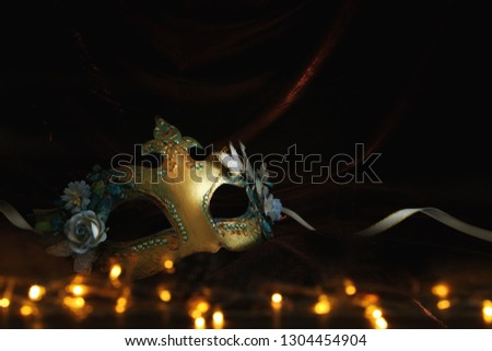 Photo of elegant and delicate gold venetian mask over dark velvet and silk background #1304454904