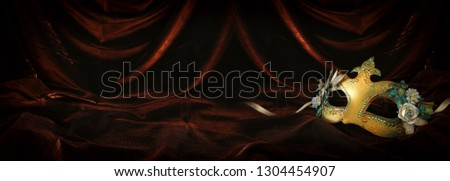 Photo of elegant and delicate gold venetian mask over dark velvet and silk background #1304454907