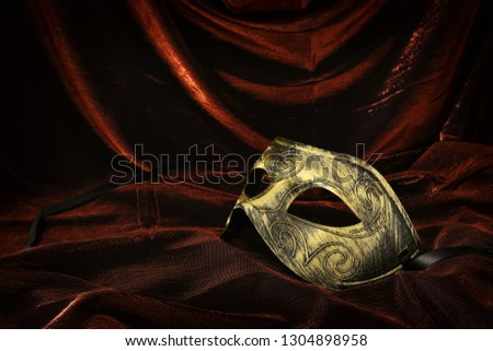 Photo of elegant and delicate gold venetian mask over dark velvet and silk background #1304898958
