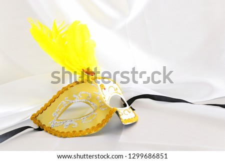 Photo of elegant and delicate gold venetian mask over white silk background #1299686851