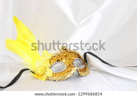 Photo of elegant and delicate gold venetian mask over white silk background #1299686854