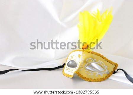 Photo of elegant and delicate gold venetian mask over white silk background #1302795535
