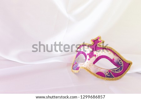 Photo of elegant and delicate pink, purple and gold venetian mask over white silk background #1299686857