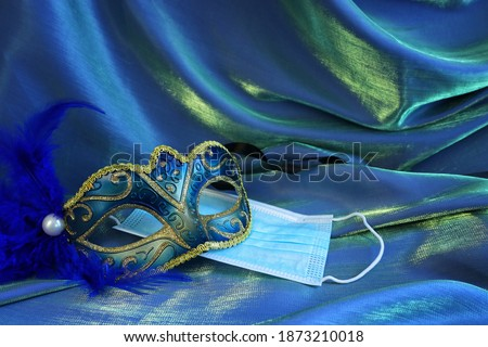 Photo of elegant and delicate Venetian mask over blue silk background. Coronavirus prevention concept