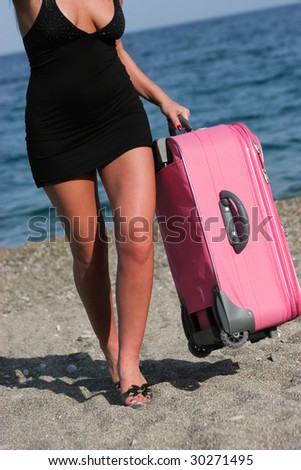 Photo of elegant female carrying pink suitcase while walking down sandy beach