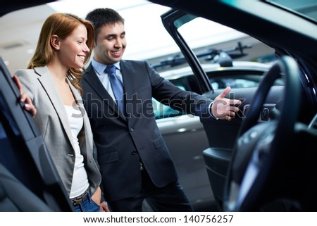 Photo of elegant woman listening to consultant in automobile center #140756257