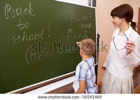 Photo of elementary student writing formulae on blackboard with his teacher near by