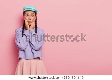 Photo of emotional Asian woman with stunning look, forgets about something important, looks away on free space, dressed in stylish clothes, poses over pink wall. People, face expressions, reaction