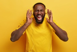 Photo of emotional black man keeps hands on yellow headphones, screams while listens punk music with high volume, has thick bristle, isolated. Monochrome. Emotions, leisure, ethnicity concept