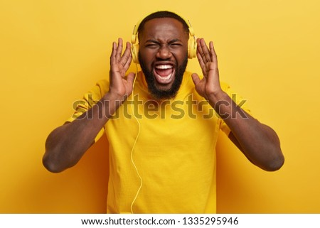 Photo of emotional black man keeps hands on yellow headphones, screams while listens punk music with high volume, has thick bristle, isolated. Monochrome. Emotions, leisure, ethnicity concept #1335295946