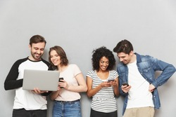 Photo of emotional group of friends standing isolated over grey wall background chatting by mobile phones and laptop computer.