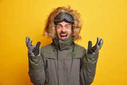 Photo of emotional irritated snowboarder raises hands and shouts loudly expresses negative emotions wears winter jacket with ski goggles gloves gestures actively keeps mouth opened isolated on yellow