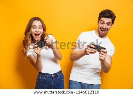 Photo of emotional young man and woman playing together video games using smartphones isolated over yellow background #1146012110