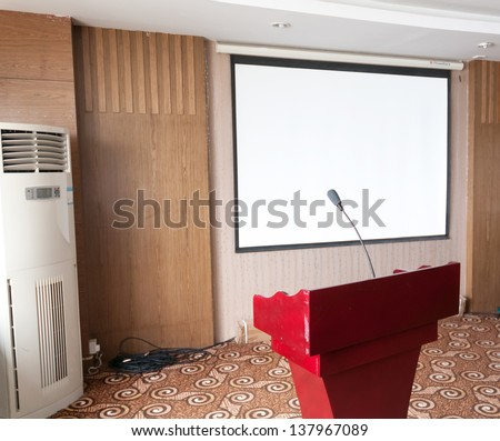 Photo of empty conference room with microphones and blank