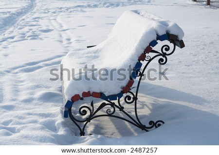 Photo of empty park bench covered with winter snow