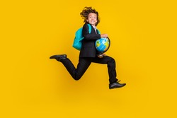 Photo of energetic little boy jump rush run hold globe wear rucksack black uniform isolated yellow color background