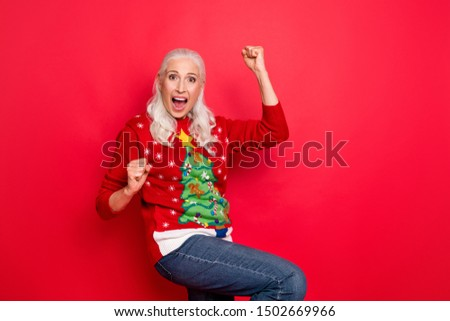 Photo of enthusiastic funky retro model granny having fun good mood gesturing raising fists up wearing jeans denim bright jumper isolated vivid color background
