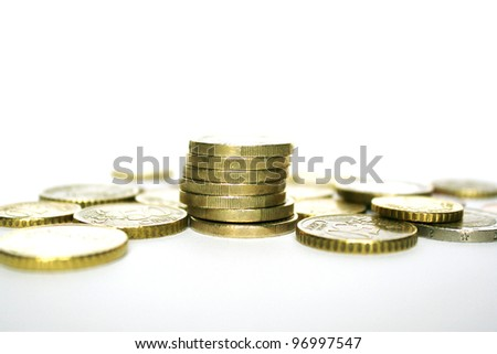Photo of euro coins with some stacked on each other on white and grey background - stock photo