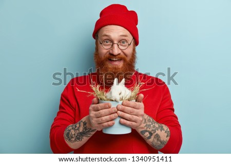 Photo of European blue eyed man with thick bristle, has glad facial expression, holds tiny white rabbit, buys symbol of Easter holiday, smiles positvely, wears red outfit, models over blue studio wall