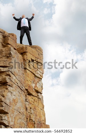 Photo of excited business man standing on the mountain