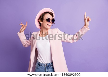 Photo of excited dance disco hit young brunette woman wear cap glasses coat isolated on purple color background
