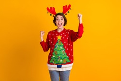 Photo of excited girl in christmas tree sweater pullover deer headband balls raise fists x-mas time noel lottery sale win isolated over bright shine color background