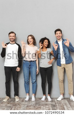 Photo of excited group of friends standing isolated over grey wall background looking camera make okay gesture.