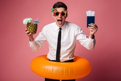 Photo of excited happy young businessman with rubber ring standing isolated holding passport with tickets and cocktail. Looking at camera.