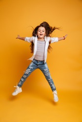 Photo of excited little girl child jumping isolated over yellow background. Looking camera.