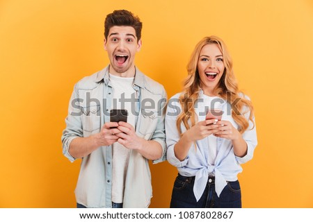 Photo of excited people man and woman rejoicing while holding smartphones in hands isolated over yellow background #1087802867