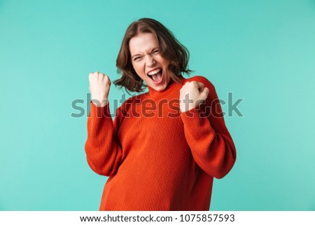 Photo of excited woman standing isolated over blue background looking camera make winner gesture.
