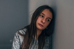 Photo of Expression of lonely female teenager at home. Portrait of a sad teenage girl looking thoughtful about troubles. Pensive teen. Depression, teen depression, pain, suffering.