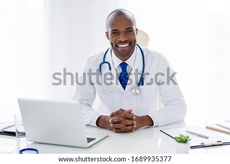 Photo of family doc dark skin cheer guy toothy smile consultant notebook table prescription help patients control panic fear risk epidemic disease wear white lab coat office clinic indoors