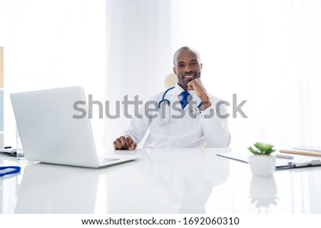 Photo of family doc dark skin guy online consultation use notebook tell write give prescriptions help people control panic risk epidemic wear white lab coat sit chair office clinic indoors