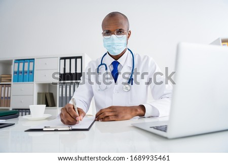 Photo of family doc dark skin professional guy write prescriptions patients insurance expensive hospital wear protective viral mask white lab coat sit chair modern office clinic indoors
