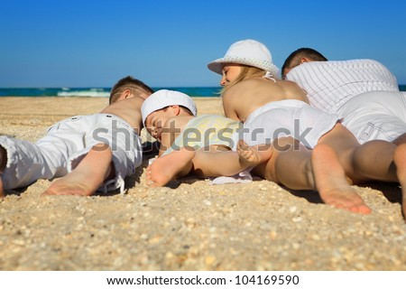 Photo of  family lying on sand on background of blue sky