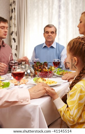 Photo of family members giving thanks to God at festive table while holding each other by hands