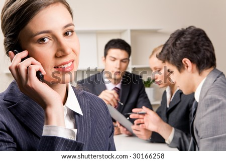 Photo of female employee speaking on the phone with smile